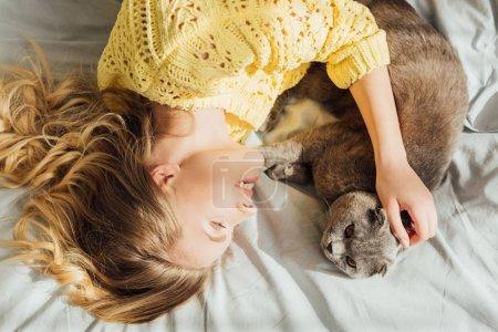 Photo pour Vue de dessus de belle fille souriante caressant le chat de pli écossais tout en se trouvant dans le lit à la maison - image libre de droit