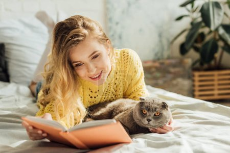 Photo pour Beau livre de lecture de jeune femme souriant tout en se trouvant dans le lit avec le chat écossais de pli - image libre de droit