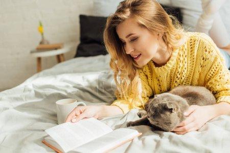 Photo pour Belle jeune femme lecture livre tout allongé dans le lit avec écossais plier chat - image libre de droit