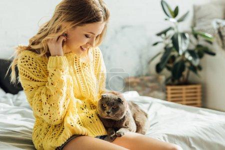 Photo pour Foyer sélectif de belle jeune femme blonde souriante assise sur le lit avec chat pliant écossais - image libre de droit