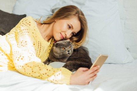 Photo pour Belle jeune femme prenant selfie sur smartphone tout en étant couché au lit avec chat pliant écossais - image libre de droit