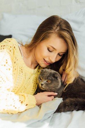 Photo pour Belle jeune femme en chandail tricoté couché dans le lit et câlin écossais plier chat - image libre de droit