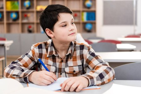Photo for Pensive brunette pupil in checkered shirt writing in notebook during lesson - Royalty Free Image