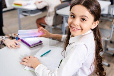 Foto de Alegre colegiala sonriente sentada en el escritorio y mirando a la cámara en el aula - Imagen libre de derechos