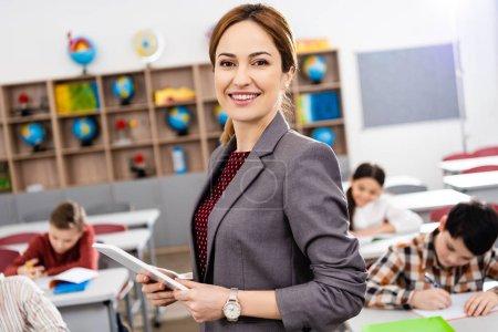 Photo pour Professeur souriant avec la tablette numérique restant devant des élèves et regardant l'appareil-photo - image libre de droit