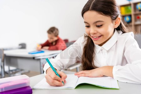 Photo for Smiling schoolgirl writing in notebook during lesson in classroom - Royalty Free Image