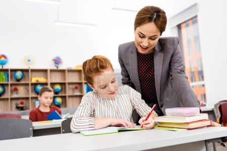 Foto de Profesor parado cerca del escritorio y explicando la lección al alumno en el aula - Imagen libre de derechos