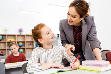 Photo for Teacher standing near desk and explaining lesson to pupil in classroom - Royalty Free Image