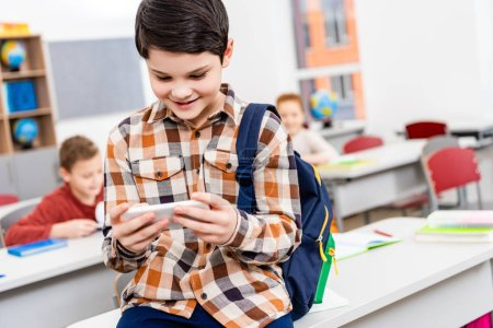 Photo for Smiling pupil in checkered shirt with backpack using smartphone in classroom - Royalty Free Image