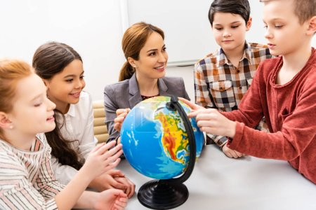 Teacher and pupils looking at globe while studying geography in classroom
