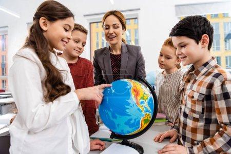 Photo pour Enseignant et élèves regardant le globe tout en étudiant la géographie dans la salle de classe - image libre de droit