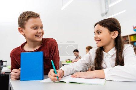 Photo pour Écolière souriante parlant avec un ami tout en écrivant dans un carnet de notes en classe - image libre de droit