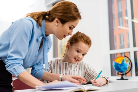 Photo pour Enseignant en chemisier bleu expliquant la leçon à l'élève en classe - image libre de droit