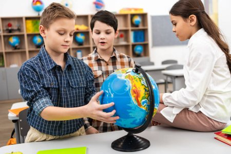 Photo for Three cheerful pupils playing with globe in classroom during geography lesson - Royalty Free Image
