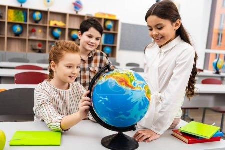 Photo pour Trois élèves joyeux jouant avec le globe en classe pendant la leçon de géographie - image libre de droit