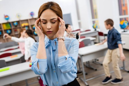Photo pour Tired teacher in blue blouse standing in front of desks and touching face - image libre de droit