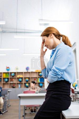 Foto de Profesor cansado de blusa azul parado cerca de la mesa en el aula - Imagen libre de derechos