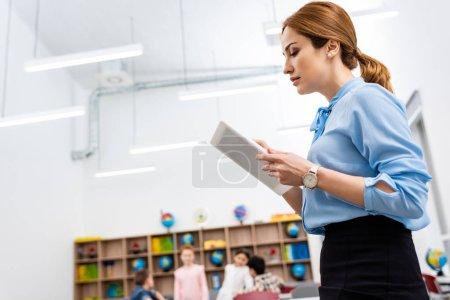 Foto de Profesora seria de blusa azul con tableta digital en aula - Imagen libre de derechos