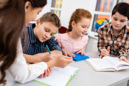 Photo pour Quatre élèves avec cahier et livres au bureau en classe - image libre de droit
