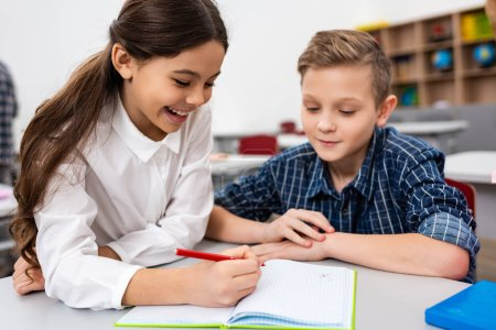 Photo for Two pupils writing in notebook at desk in classroom - Royalty Free Image