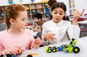 """Постер, картина, фотообои """"Ученики сидят за столом с образовательными игрушками во время урока в классе"""""""