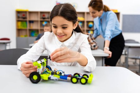 Photo for Smiling schoolgirl playing with educational toy during lesson in class - Royalty Free Image