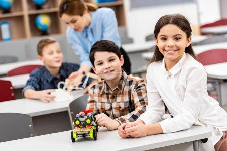 Photo pour Elèves assis au bureau avec des jouets pendant les cours en classe - image libre de droit