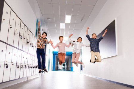 Photo for Four smiling pupils jumping in corridor during brake in school - Royalty Free Image