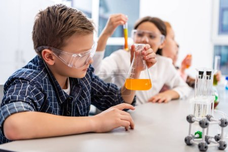 Photo pour Pupils in protective goggles holding beakers during chemistry lesson - image libre de droit