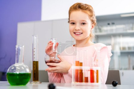 Photo for Smiling schoolgirl holding beaker and looking at camera during chemistry lesson - Royalty Free Image
