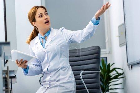 Photo pour Professeur de chimie en manteau blanc à l'aide d'une tablette numérique et pointant la main dans la classe - image libre de droit