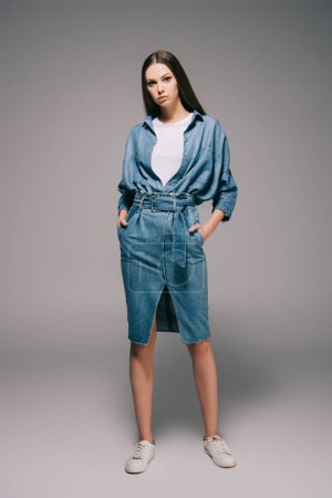 Photo for Young adult and beautiful woman in denim dress with hands in pockets looking at camera - Royalty Free Image