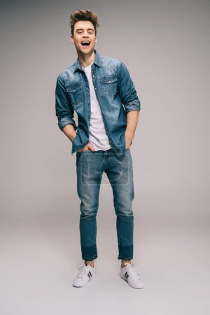 Photo for Smiling and good-looking man in jeans, skirt and t-shirt with hands in pockets looking at camera - Royalty Free Image