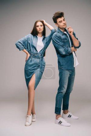 Photo pour Superbe copine en robe en denim et beau petit ami en jeans et chemise sur fond gris - image libre de droit