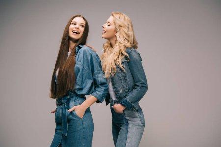 Photo pour Femmes blondes et brunes en denim souriant sur fond gris - image libre de droit