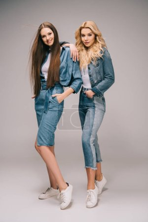 Photo for Blonde and brunette women in denim clothes with hands in pockets smiling and looking at camera - Royalty Free Image
