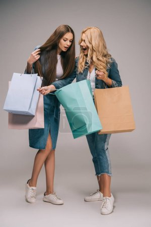 Photo for Surprised blonde and brunette women in denim clothes holding shopping bags - Royalty Free Image