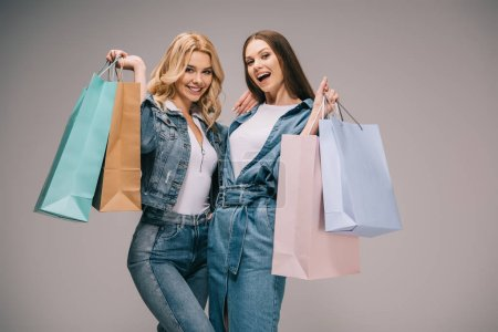 Photo for Beautiful blonde and happy brunette women in denim clothes holding shopping bags and smiling - Royalty Free Image