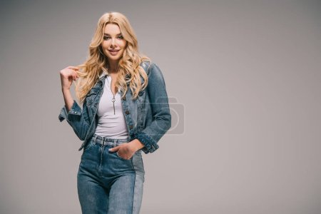 Photo for Attractive blonde woman in denim clothes with hand in pocket smiling and looking at camera - Royalty Free Image