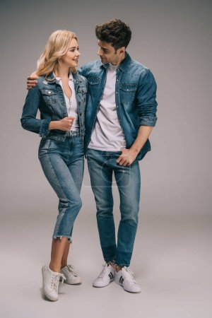 Photo for Boyfriend and girlfriend in denim clothes hugging and looking at each other - Royalty Free Image