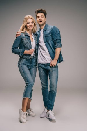 Photo for Boyfriend and girlfriend in denim clothes hugging and looking at camera - Royalty Free Image