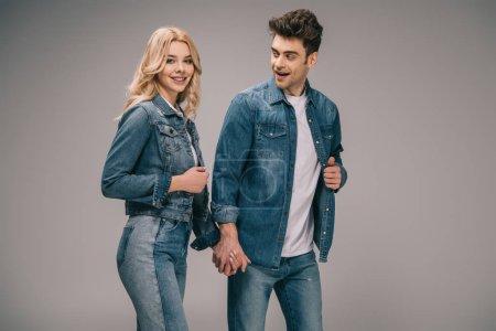 Foto de Sonriendo el novio y la novia atractiva en ropa vaquera cogidos de la mano sobre fondo gris - Imagen libre de derechos
