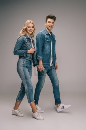 Photo for Smiling boyfriend and attractive girlfriend in denim clothes holding hands and looking at camera - Royalty Free Image