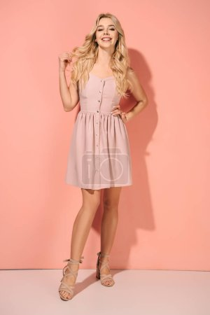 Photo for Blonde and beautiful woman with hand on hip in pink dress smiling and looking at camera - Royalty Free Image