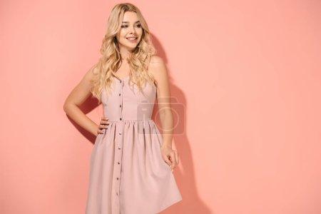 Photo pour Blonde et belle femme avec la main sur la hanche dans une robe rose en souriant et en regardant loin - image libre de droit