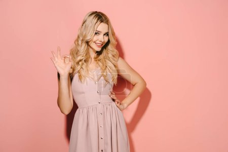 Photo for Attractive and blonde woman in pink dress with hand on hip showing okay - Royalty Free Image
