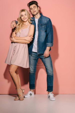 Photo for Smiling girlfriend in pink dress and handsome boyfriend in denim shirt hugging and looking at camera - Royalty Free Image