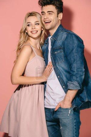 Foto de Novia sonriente en vestido rosa y el novio guapo en camiseta denim abrazar y mirar a - Imagen libre de derechos