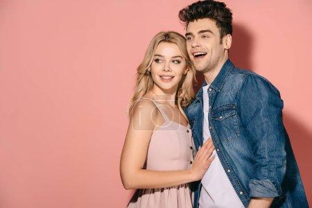 Photo pour Petite amie souriante en robe rose et beau petit ami en chemise denim étreignant et détournant les yeux - image libre de droit