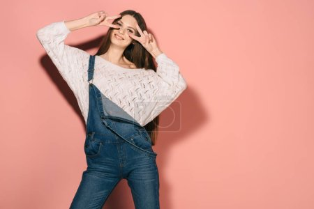 Photo for Brunette and beautiful woman in denim overalls showing victory gestures - Royalty Free Image